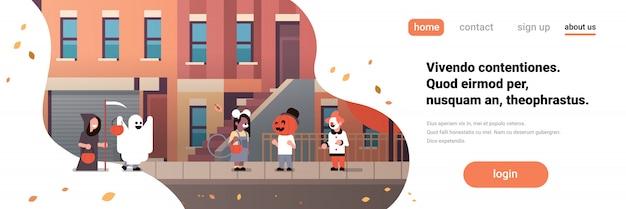 Kids wearing monsters ghost pumpkin wizard clown costumes walking town banner
