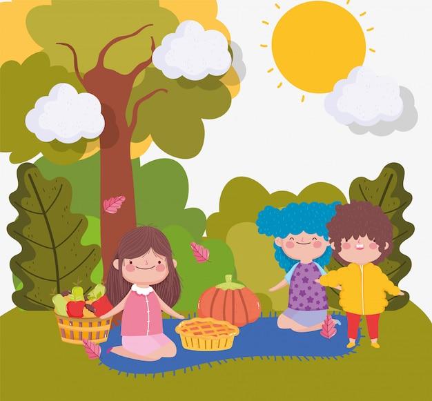 公園で毛布の上に食べ物を持つ子供