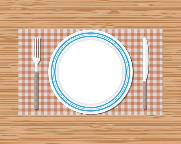 Нож, вилка, тарелка, красная клетчатая ткань, деревянный стол