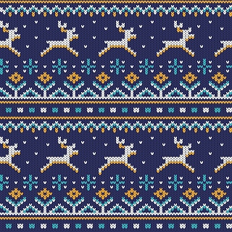 Knitted seamless ornament with running deer on a blue background.