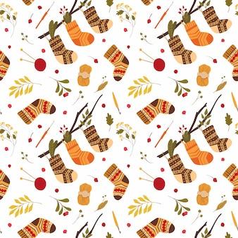 木にぶら下がっている民俗装飾品とシームレスなパターンの暖かい冬の靴のニットウールソックス