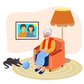編み物老婆は、毛糸の玉で遊んでいる猫の隣の肘掛け椅子で編み物をしているおばあちゃんを編みます