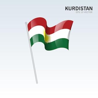 灰色に分離されたクルディスタンの旗を振っています。