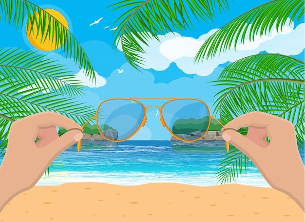 ビーチの風景、サングラスをかけた手。