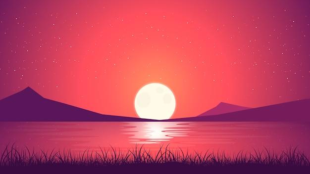 海岸に沈む夕日の風景。明るい水と山脈の上の草のシルエット。