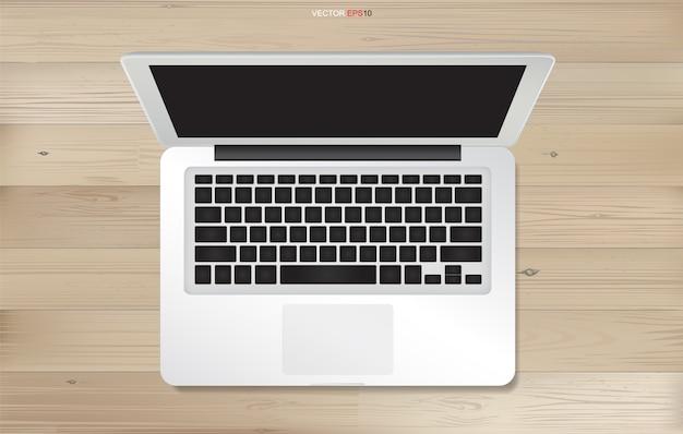 木製のテクスチャの背景にノートパソコン。