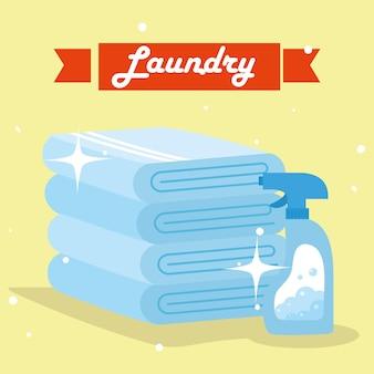 노란색 배경에 세제 스프레이가 있는 세탁 수건
