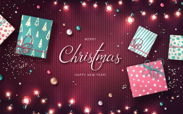 クリスマスライト、つまらないもの、ギフトボックス、紙吹雪とクリスマスの背景。ニットの質感のled電球の休日輝く花輪。年賀状用のリアルなカラフルなランプの装飾