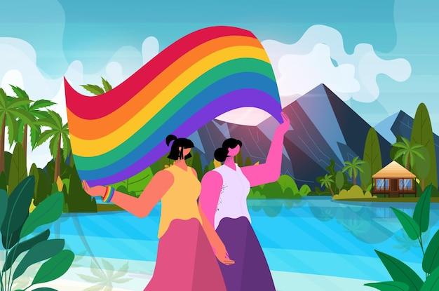 무지개 깃발을 들고 레즈비언 커플 트랜스젠더 사랑 lgbt 커뮤니티 개념 바다 배경