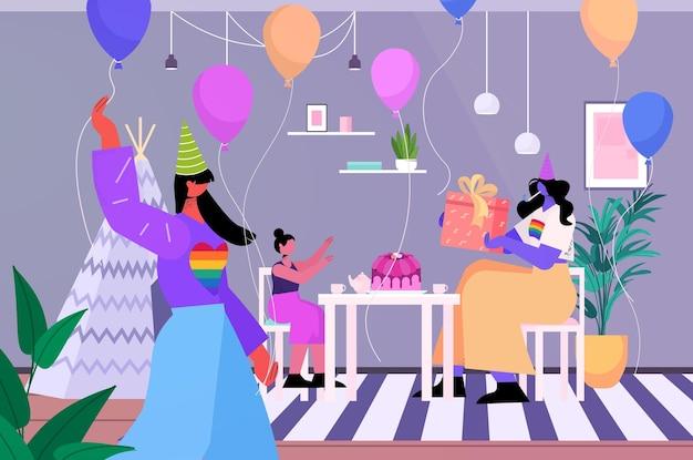 어린 딸 lgbt 프라이드 퍼레이드 트랜스젠더 사랑 개념과 함께 생일 파티를 축하하는 레즈비언 여성 부모
