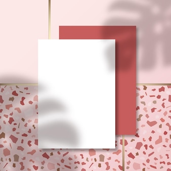 Letterheads on terrazzo tile floor pattern surface with a tropical monstera palm leaves shadow overlay
