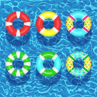 スイミングプールに浮かぶ生命ブイ。背景に水のビーチゴムリング。ライフブイ、子供向けのかわいいおもちゃ。不可能円。人を救うためのレスキューベルト。