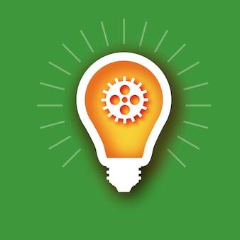 内側の電球と歯車はペーパーカットスタイルです。歯車と歯車が連動する折り紙電球。ビジネスアイデアの概念。チームワーク。戦略。協力。緑の背景。