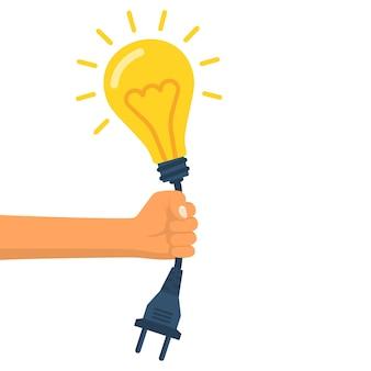 ワイヤーと電気プラグが手を握って電球。黄色の光。電気ランプ。イラストフラットデザイン。白い背景で隔離されました。