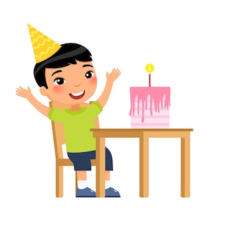 Little asian boy with birthday cake with candle on table
