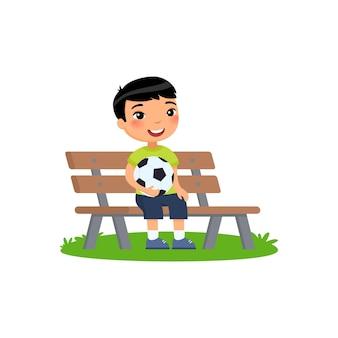 그의 손에 축구 공 가진 작은 아시아 소년 벤치에 앉아있다. 여름 방학, 레크리에이션, 스포츠, 취미.