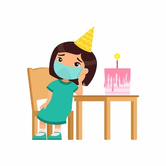 아시아 소녀는 그녀의 생일에 슬프다. 그의 얼굴에 의료 마스크와 귀여운 아이가 의자에 앉아있다. 혼자 생일. 바이러스 보호, 알레르기 개념.