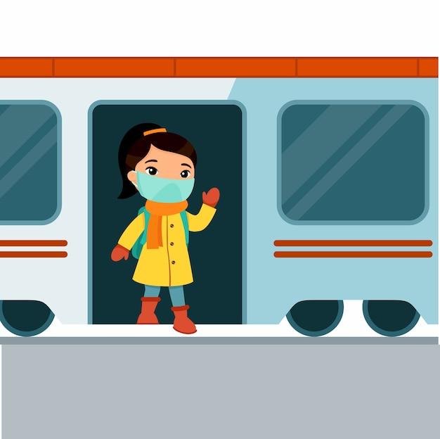 Маленькая азиатская девушка выходит из поезда и машет рукой. милая школьница с медицинской маской на лице. концепция защиты от вирусов в общественном транспорте