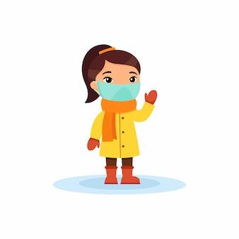 Маленькая азиатская девушка с респираторной маской на лице машет рукой. защита от вируса. симпатичный плоский персонаж в зимней одежде.