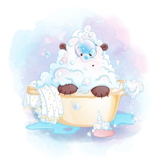 un cucciolo di orso in schiuma insaponata siede in una vasca da bagno e guarda una bolla di sapone sul naso.