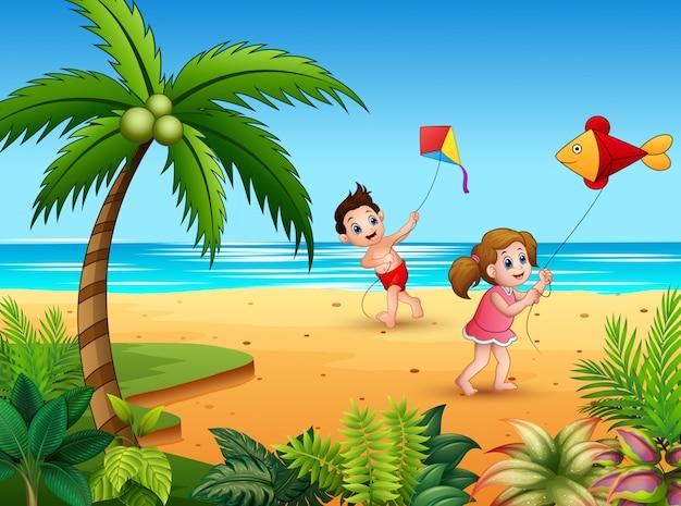 男の子と女の子がビーチでkitで遊ぶ