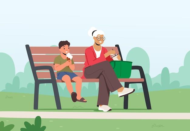 Маленький мальчик и бабушка едят мороженое в городском парке