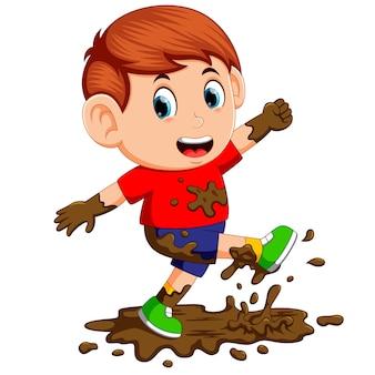 小さな男の子は泥で遊ぶことを楽しむ