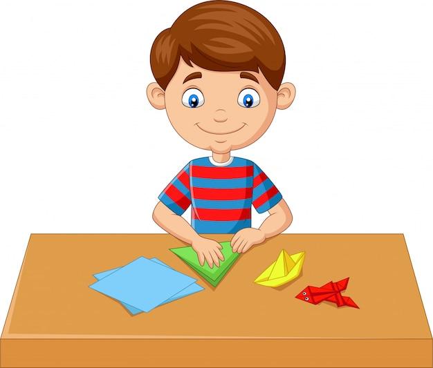 小さな男の子が紙を折ると折り紙のおもちゃを作る