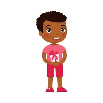 お祝いのギフトボックスを保持している小さな男の子。驚きの笑顔の子供のキャラクター。