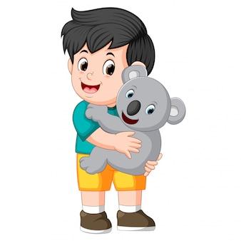 A little boy holding koala