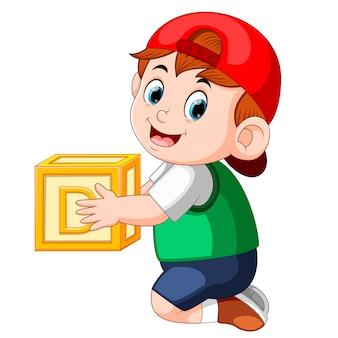 Маленький мальчик, держащий кубик алфавита