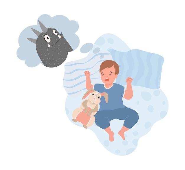 밤에 잠자는 귀여운 파란색 옷을 입은 어린 소년과 악몽이 있습니다.