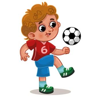 운동복을 입은 어린 소년이 축구공을 가지고 놀고 있다