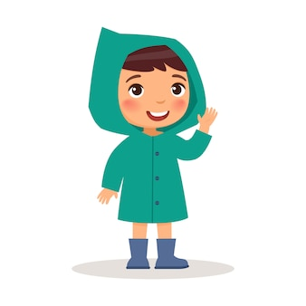 Little boy is standing in a turquoise raincoat and blue rubber boots.