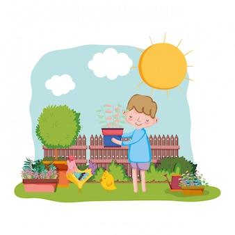 フェンスとオンドリの観葉植物を持ち上げる少年