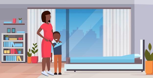 Маленький мальчик слушая беременная мать живот беременная женщина с сыном ожидание