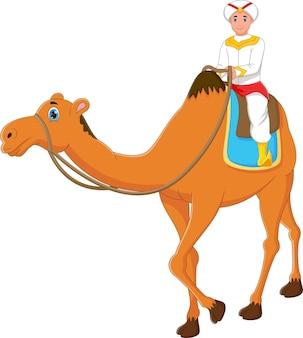 白い背景の上のラクダに乗って小さな男の子