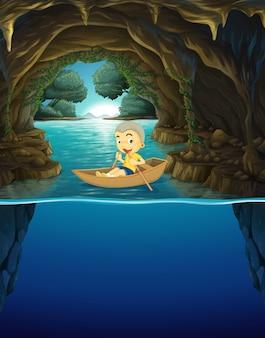 Маленький мальчик гребная лодка в пещере
