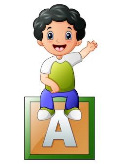 Little boy sitting on alphabet cube