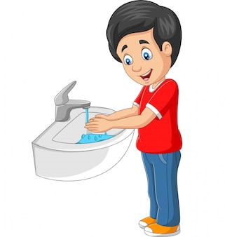 Маленький мальчик моет руки на белом