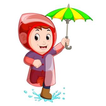 Little boy wearing raincoat and holding umbrella