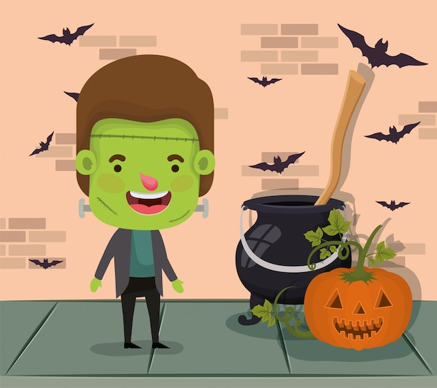 Little boy with costume of frankenstein and cauldron and pumpkin