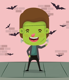 Little boy with costume of frankenstein in wall and bats flying
