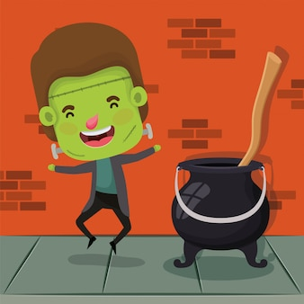 Little boy with costume of frankenstein and witch cauldron