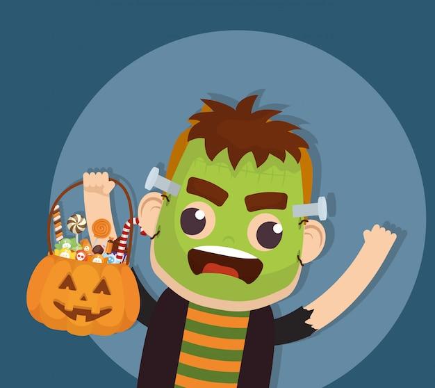 Little boy with frankenstein disguise and candies pumpkin