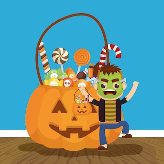 Little boy with frankenstein disguise and candies pumpkin