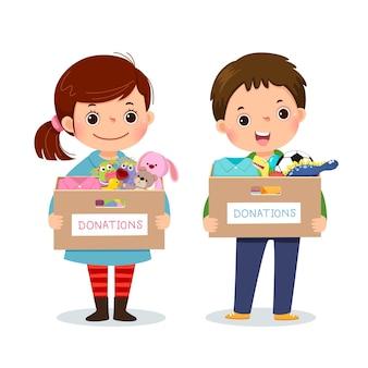 어린 아이 소녀와 소년 옷과 장난감 기부 상자를 들고