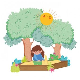 Маленькая пухлая девочка играет в песочнице