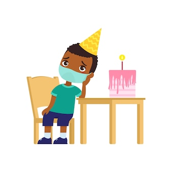 Little dark skin boy is sad on her birthday. cute kid with a medical mask on his face sits on a chair. birthday alone. virus protection, allergies concept.