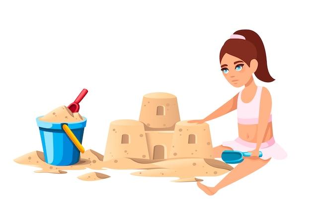 Маленькая девочка построила простой замок из песка с ведром и красной лопатой